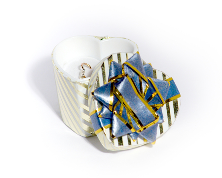 millboard: Photo of a gift striped box with a cover and dark blue bow in the form of an ornament. In packing gold ear rings lay. Focus of a photo on a gold product inside of a box. The image separately on a white background Stock Photo