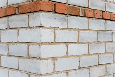 Basis: Corner of the house constructed on the basis of a silicate and ceramic brick. A background on a theme about construction. Stock Photo