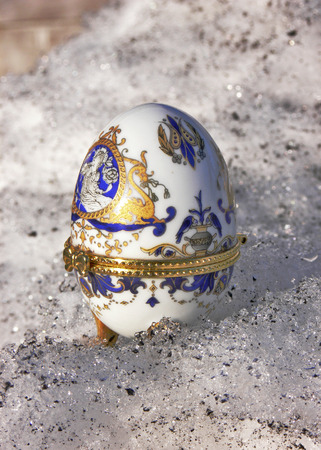 thawed: The decorative ceramic easter egg with a gold surrounding rim stands on a spring thawed snow and is shined by a warm sunlight