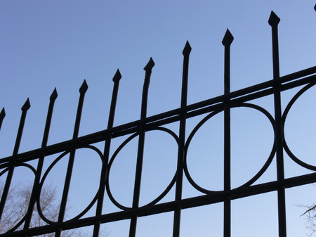 Part of a high metal fence on a background of the blue sky