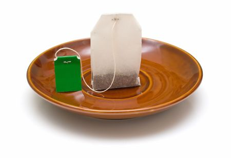 Tea bag on a brown plate. The composition symbolizes a small break, a pause or a dinner. Isolation. photo