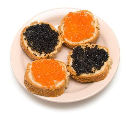 Sandwiches with red and black fish caviar on a plate photo