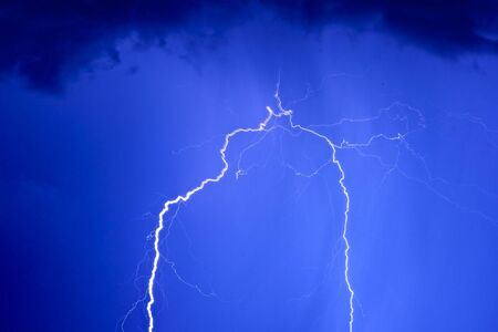 streak lightning: Photo of a lightning during a thunder-storm on a background of the dark dark blue sky Stock Photo
