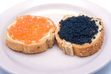 Sandwiches with red and black fish caviar on a plate. Shallow DOF. photo