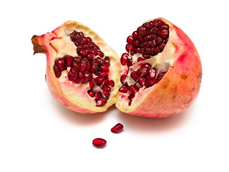 The pomegranate divided into parts. The juicy fruit containing set of vitamins, useful to a human body. Isolation on white. Shallow DOF. Stock Photo