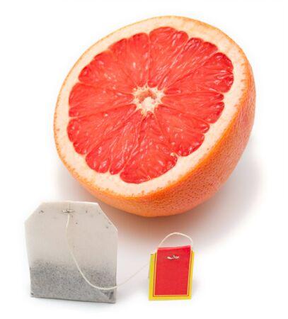 Tea bag on a background of a ripe grapefruit. Isolation on white. Shallow DOF, focus on a tea bag. photo