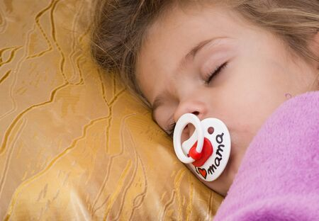nipple girl: Cute little girl sleeping. Sleeping happiness. Little girl sleeping with a pacifier in the purple overall. On the nipple inscription - Ilove mama, blonde hair on a golden pillow. Stock Photo