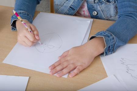 upbringing: Hand of a child drawing on white paper, pencil