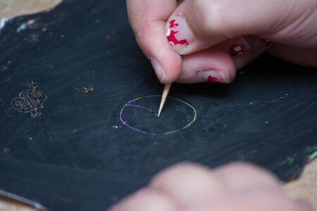 stilus: A kids hand writing on a blackboard, scrached with stilus