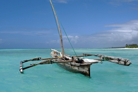catamaran: Characteristic old fishermans boat in the crystal blue ocean near Zanzibar.