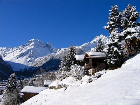 Chalets in una valle di neve bianca, nelle Alpi svizzere, in una giornata limpida. Archivio Fotografico