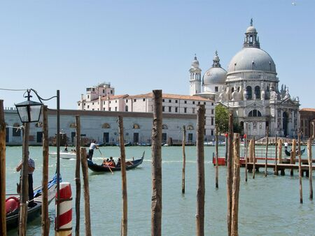 sante: Gondolas on the Grand Canal with the Sante Maria della Salute church in Venice, Italy. Stock Photo