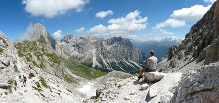 rosengarten: Male sitting on top of the world. View from Catinaccio (Rosengarten) mountain in the Italian Dolomites.