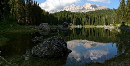 Reflection of the Dolomites in Italy in the quiet Carezza Lake photo