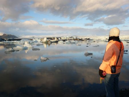 calving: Young woman admiring Jokulsarlon, a lake in Iceland, where icebergs collapsing from Vatnajokull glacier are floating around.