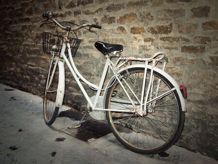 florence: Worn vintage bicycle against an old brick wall. Stock Photo