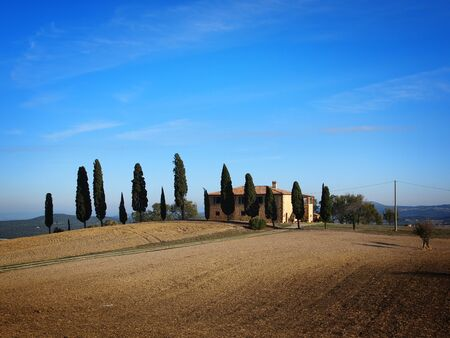 agriturismo: Typical farmhouse with cypress trees near Pienza in the Val d'Orcia in Tuscany, Italy. Stock Photo