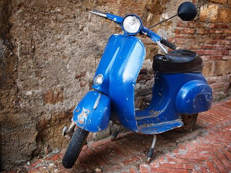 vespa: Typical italian retro style scooter parked in front of a brick wall.