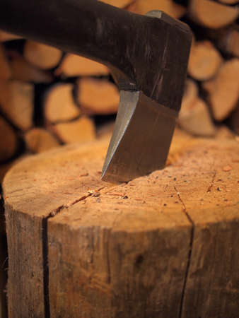 Close-up shot of an axe in a stump with firewood in the background. photo