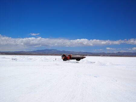 salar: Piles of drying salt and people harvesting salt with a very old truck at the Salar de Uyuni (salt flats) in Bolivia.