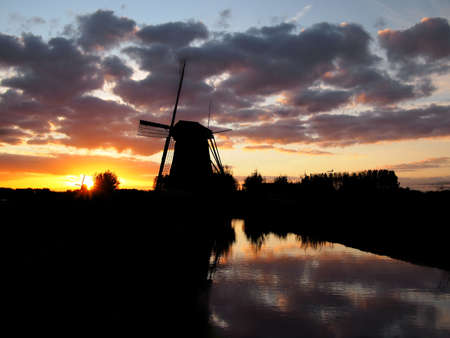 dutch windmill: Silhouette of a windmill next to a canal during sunset in the Netherlands.