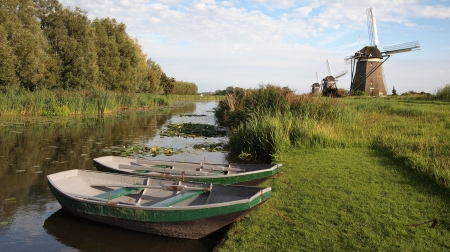Landscape in Holland with windmills and canal with rowing boats  photo