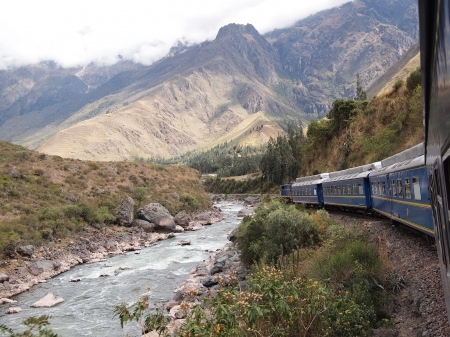 cuzco: Blue train in a mountain landscape next to a white water river heading from Cuzco through the sacred valley to the Inca city of Machu Picchu in Peru