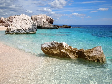di: Big rocks and shallow emerald sea at Cala Mariolu, a beach in the Golfo di Orosei, Sardinia, Italy.