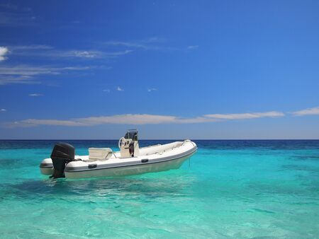 speedboat: Speedboat in a tropical looking emerald sea Stock Photo