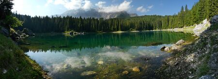 Reflection of the Latemar in the incredibly clear blue Carezza Lake in the Italian Dolomites. photo