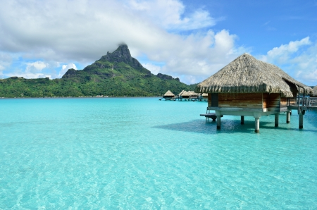 Luxury overwater bungalow in a vacation resort in the clear blue lagoon with a view on the tropical island of Bora Bora, near Tahiti, in French Polynesia  Stock Photo