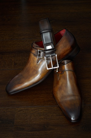 Luxury italian style brown leather shoes and belt for him against a dark background. Stock Photo