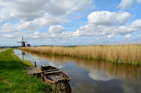 holland landscape: Typical landscape in Holland with an old boat in a ditch with a windmill, reeds and clouds.