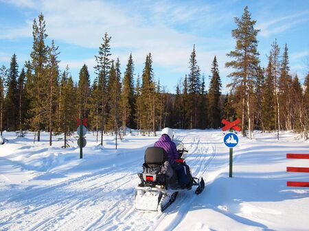 Person on a snow mobile on a track with a snow mobile traffic sign. photo