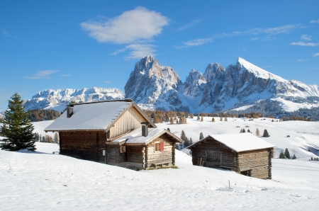 Wooden mountain chalets with a view on the Langkofel and Plattkofel (Sassolungo and Sassopiatto) dolomites mountains at the Alpe di Siusi or Seiser Alm in South Tyrol, Italy in winter.