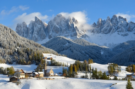 St. Magdalena or Santa Maddalena with its characteristic church in front of the Geisler or Odle dolomites mountain peaks in the Val di Funes (Villnosstal) in Italy in winter. Stock Photo