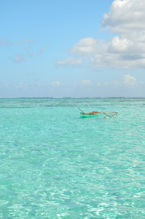 french polynesia: Outrigger canoe in the clear water of the blue lagoon of Bora Bora island in the Tahiti archipelago French Polynesia. Stock Photo