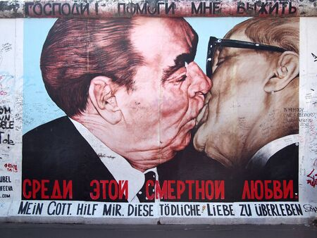 Berlin, Germany - August 29, 2012: The most famous part of the remains of the Berlin Wall. The kiss of Erich Honecker and Leonid Brezhnev, presidents of GDR and USSR.