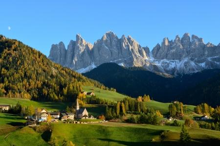 Santa Maddalena o Santa Maddalena, con la sua caratteristica chiesa di fronte alla Geisler Odle o Dolomiti picchi di montagna in Val di Funes (Val di Funes) in Italia in autunno.