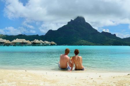 luna de miel: Una pareja de reci�n casados ??beber un c�ctel en la playa de un centro tur�stico de lujo en la laguna, con una vista de la isla tropical de Bora Bora, cerca de Tahit�, en la Polinesia Francesa.