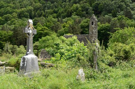 monastic site: A celtic cross on the overgrown graveyard next to the medieval church of St. Kevin at the monastic heritage site Glendalough, south of Dublin in Ireland.