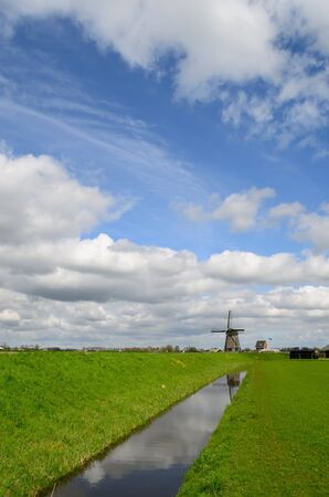 coutryside: Dutch clouds in the sky over a windmill, a meadow, a ditch and a dike in Holland.
