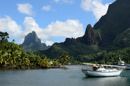 moorea: Boat in Cooks Bay with Moua Puta mountain in the background on the tropical pacific island of Moorea, near Tahiti in French Polynesia