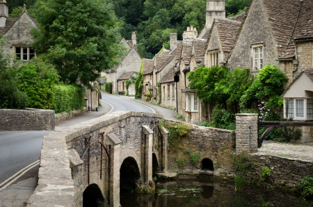 wiltshire: The quaint fairy tale village of Castle Combe at the border between the Cotswolds and Wiltshire with its characteristic bridge  Rural England at its best  Editorial