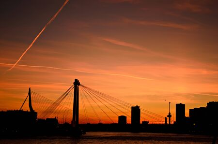 maas: The skyline of the city of Rotterdam in the Netherlands over the water of the river Maas during sunset