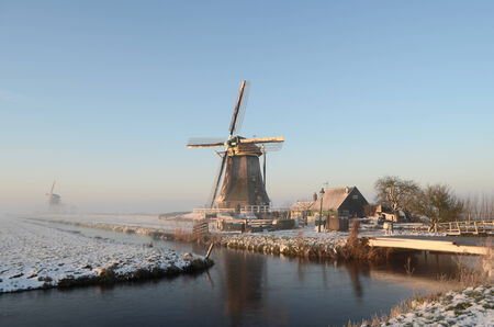 Typical winter landscape in Holland  the Netherlands  with a windmill, a canal, snow and fog  photo