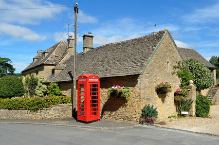 telephone box: Honey coloured stone houses and a red telephone box in a village in the Cotswolds in rural England