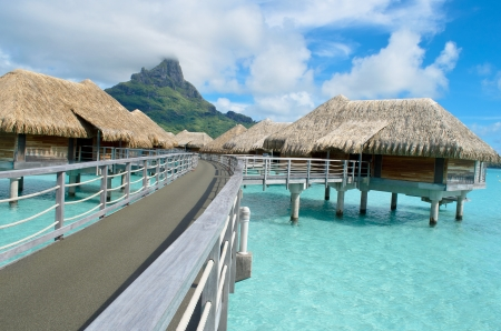 thalasso: bungalows sur pilotis de luxe dans un lieu de villégiature dans le lagon bleu clair avec une vue sur l'île tropicale de Bora Bora, près de Tahiti, en Polynésie française Éditoriale