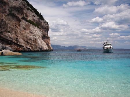 golfo: Boat arriving on a beach of Sardinia, Italy, through the emerald blue water of the Golfo di Orosei  Editorial