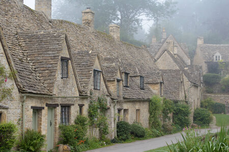 weavers: The Arlington Row, honey coloured weavers cottages in the morning fog in the town of Bibury in Gloucestershire in the Cotswolds, England, UK  The houses were built in 1380   Stock Photo